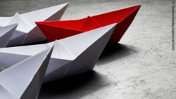 Photo: White paper boats following a red paper boat; Copyright: PantherMedia/Alphaman3000